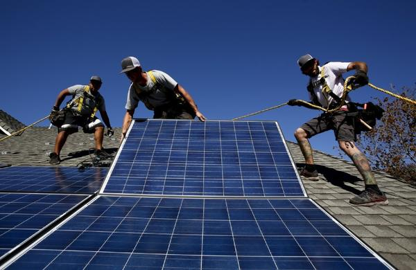 Workers install new rooftop solar panels on a house in Camarillo.