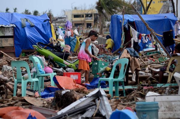 A girl rummages through debris in an area devastated by Typhoon Haiyan in the Philippines.