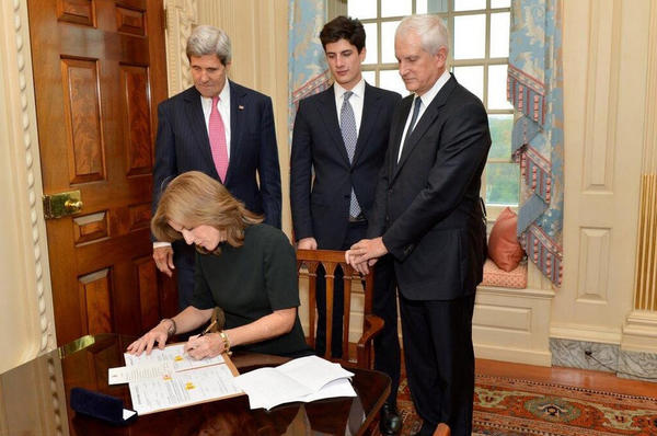 Caroline Kennedy, joined in Washington by Secretary of State John F. Kerry, left, and members of her family, signs her appointment papers to become U.S. ambassador to Japan.