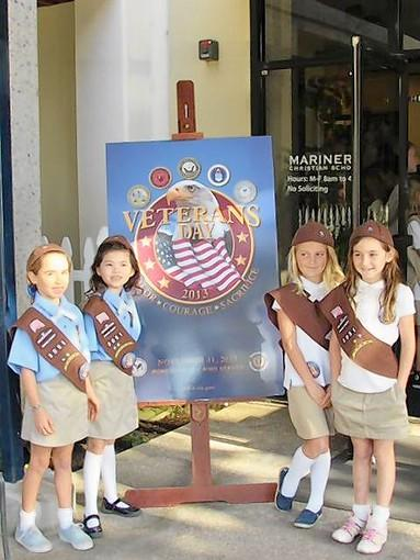 Second-grade Brownies (from left) Claire Smith, Violet Adams, Lucy Duff and Grace Monroe welcome veteran guests Monday at Mariners Christian School.