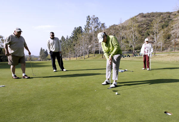 Sandra Pessaro puts one as, from left, Ed Pape, Joaquin Herbozo and Jeannie Smith look on at the 10th Annual Guys and Dolls Golf Tournament at DeBell Golf Club in Burbank on Thursday, March 15, 2012.
