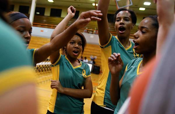 Westinghouse College Prep's Shanequa Reed, second from left, and her teammates warm up last month before a volleyball game at Gordon Tech. Reed is involved in the Center for Companies That Care's AIM High mentorship program and wants to be a nurse.