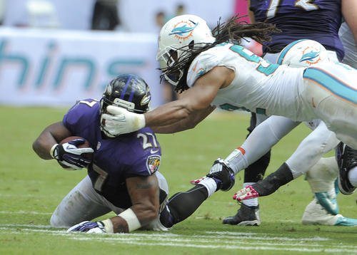 Ravens running back Ray Rice, left, is grabbed on the facemask by Dolphins linebacker Philip Wheeler in the fourth quarter.