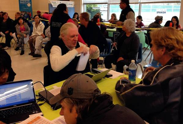 People seeking health insurance compare plans at a Washington Healthplanfinder enrollment event in Kent, Wash.
