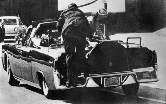 In this photo, taken just after President John F. Kennedy was hit by bullets, First Lady Jacqueline Kennedy stands up in the presidential car to lift up the body of her husband.