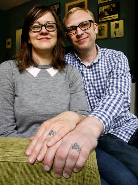 Atomic wedding ring tattoos adorning spouses Melissa Jacobson and Brent Larson remind them of a mural they saw in Mexico City.