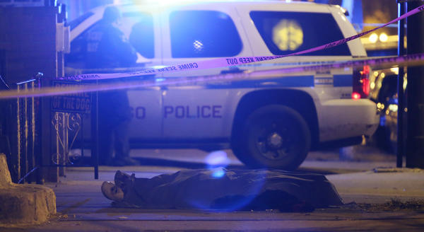 A man fatally shot lies covered on the 2300 block of South Oakley Avenue early Wednesday in Chicago.