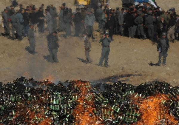 Afghan government officials and policemen watch as a cache of alcohol and drugs burns in Kabul on Tuesday.