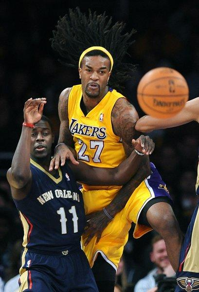 Lakers big man Jordan Hill (27) leans on New Orleans' Jrue Holiday during the Lakers' 116-95 win over the Pelicans at Staples Center on Tuesday.