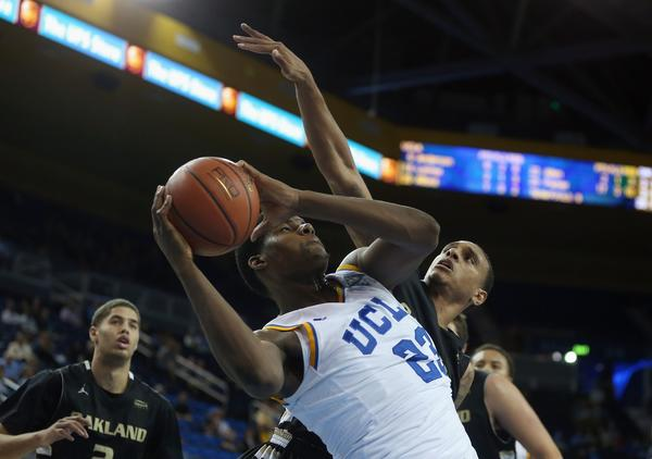 UCLA's Tony Parker is defended by Oakland's Tommie McCune on Tuesday night.