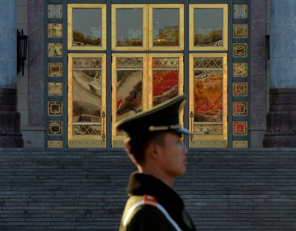 A Chinese paramilitary police officer stands guard beside the Great Hall of the People after the Communist Party Central Committee concluded its secretive Third Plenum in Beijing.