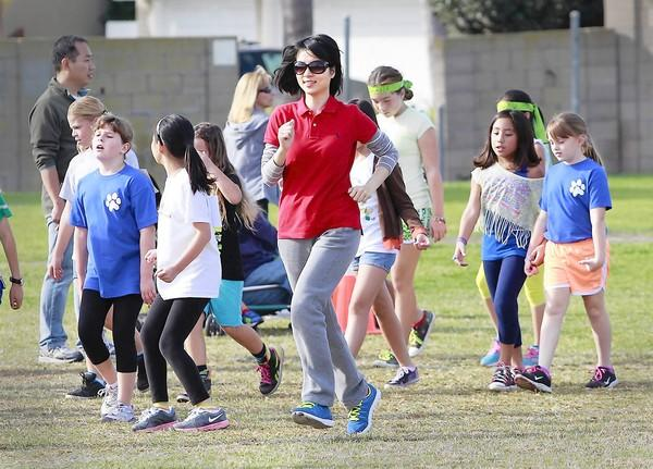 Chinese teacher Tiffany Cai laps a group of tired students as she participates in the Roch Courreges Elementary School jog-a-thon. The Chinese principals and teachers have been visiting the school all week.