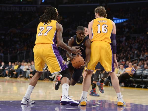 New Orleans' Jrue Holiday dribbles between Lakers Jordan Hill and Pau Gasol at Staples Center.