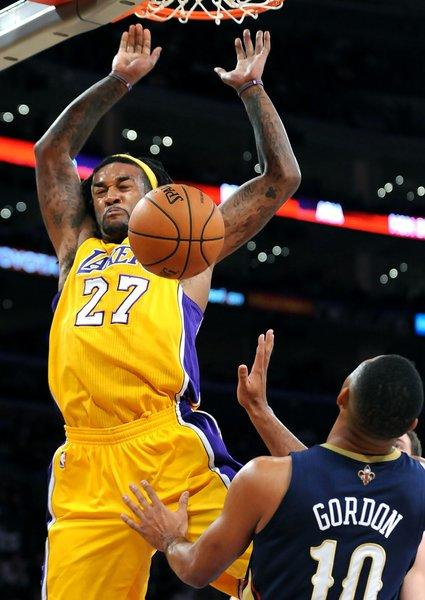 Jordan Hill dunks over Eric Gordon during the Lakers' win over the New Orleans Pelicans, 116-95, on Tuesday at Staples Center.