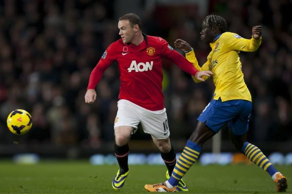 Manchester United's Wayne Rooney, left, keeps the ball from Arsenal's Bacary Sagna during their English Premier League soccer match on Sunday.