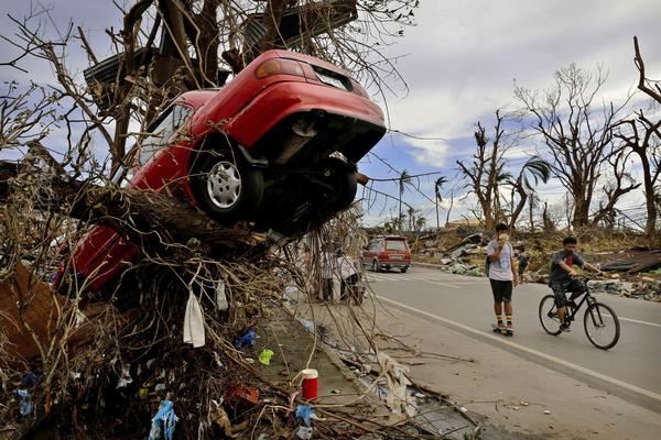 People in Tacloban, Philippines, pass scenes of devastation left by Typhoon Haiyan.