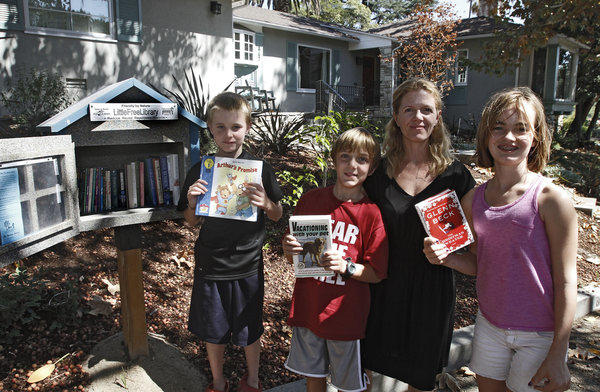 Nicole Berklas, second from right, and her children Gage, left, August, second from left, and Laura, right, in front of their home on the 800 block of West Mountain Ave., where a Little Free Library kiosk contains books, in Glendale on Saturday, September 14, 2013. People can take books, borrow books and leave books for others in the kiosk.