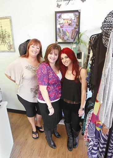Tammi Fronek, Eva and Krystal Jasperson, left to right, stand under a remembrance portrait of original 20-year stylist Julie Snyder at the Huntington Beach Hair Co.