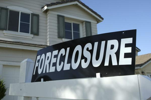 A foreclosure sign sits in front of a home for sale.