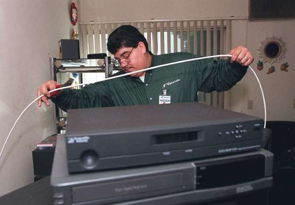 Cable companies such as Charter might be in trouble if a new report is any guide. Here, a Charter tech installs a box in 2000.