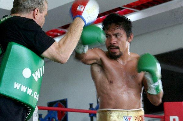 Former champion boxer Manny Pacquiao spars with trainer Freddie Roach at a gym in General Santos City last month.
