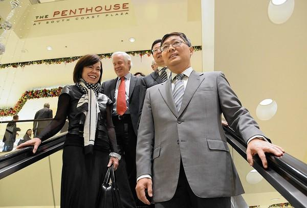 Chinese Ambassador Liu Jian, right, rides the escalator with Debra Gunn Downing, executive director of marketing, upon his arrival to South Coast Plaza Tuesday.