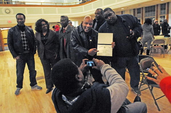 Dwight Chavis, of Bloomfield, at center, shows off his diploma for a photograph taken by his brother, Mark Jennings of Manchester, at front center, at the West Hartford Town Hall auditorium Wednesday night. The West Hartford Adult Education program graduated 25 students from around the region Wednesday.