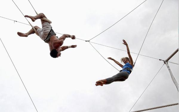 Lake Worth Circus Experience instructor Andres Leon, left, works with student Mary Mankamyer,27, of Wellington on the trapeze. The Lake Worth company gives anyone the opportunity to learn tricks, without running away with the circus.