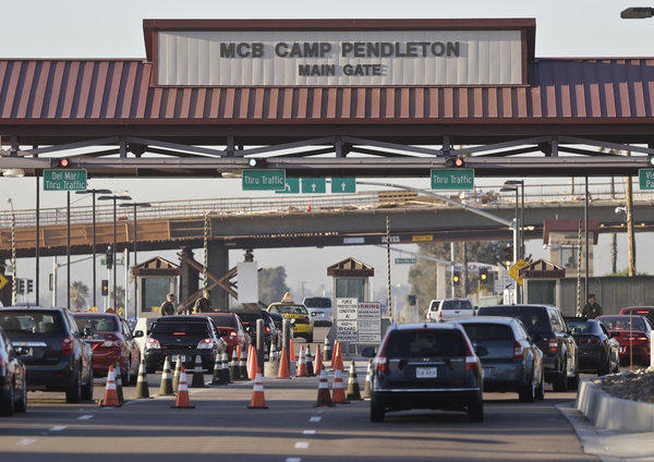 Vehicles file through the main gate of Camp Pendleton Marine Base on Wednesday. Four Marines were killed in an accident on the base.