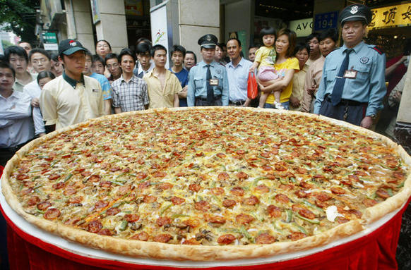 Residents look at a giant pizza with a diameter of 2 meters promoting a U.S. fast food restaurant in Guangzhou, Guangdong province, April 28, 2004.