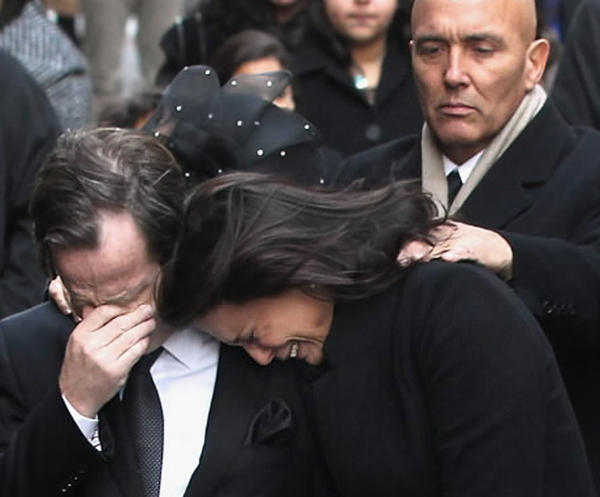 Matthew and Madonna Badger embrace as the casket of one of their three daughters is carried ahead of funeral services for the girls on January 5, 2012 in New York City.