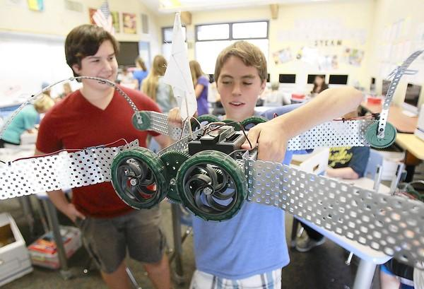 Luc LaMontagne holds a nearly finished robot on wheels as his construction partner Joey Ravenna, left, looks on in Kelly Scon's STEAM class at Thurston Middle School.