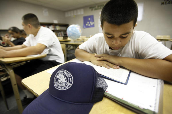 North Valley Military Institute student Edwin Perdomo, right, focuses on his book during reading time.