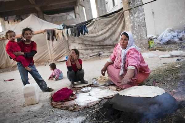 A displaced Syrian prepares bread in an abandoned factory near the northern city of Aleppo. The war in Syria has disrupted food supplies, and few scarce commodities are missed more than bread, a staple.