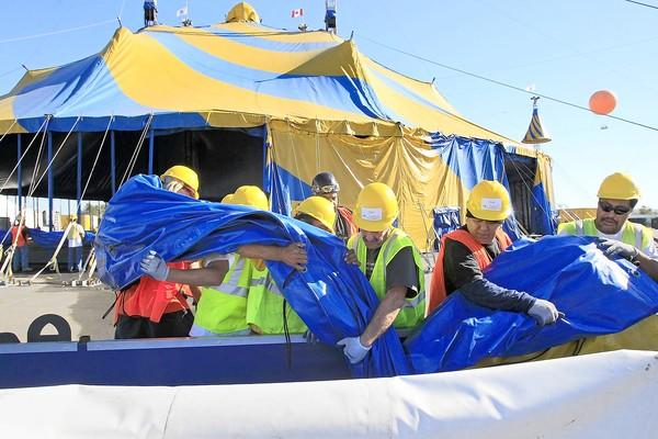 "Crew members pull out a blue-and-yellow tarp as they work on setting up Cirque du Soleil's tent in preparation for ""Totem"" at the Orange County Great Park festival site in Irvine on Thursday."
