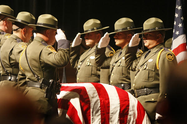 A Border Patrol honor guard stands at attention before carrying agent Robert Rosas' flag-drapped coffin during a memorial service in El Centro, Calif., in 2009.