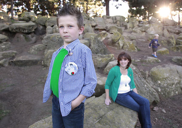 """Kieran Vogel proudly shows off a picture button of his dad Erich while his mom Bethany sits nearby during a visit to Tewinkle Park in Costa Mesa. Kieran's Halloween costume this year was his """"super hero dad"""" whose donated organs were a benefit to 64 people after his death in 2009."""