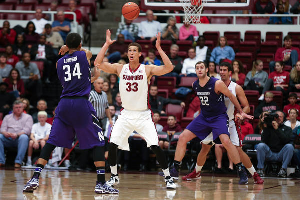 Stanford's Dwight Powell tries to block the pass from Northwestern's Sanjay Lumpkin to Alex Olah during the first half at Maples Pavilion.