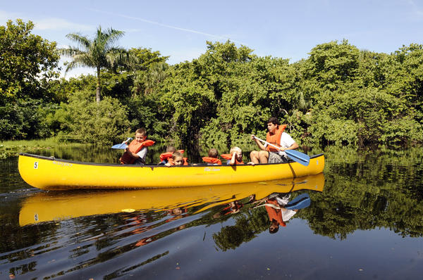 Christian Feanny, 6, with the assistance of Live Oak camp counselor Dante Medina, goes for a canoe ride with fellow campers atCamp Live Oak at Hugh Taylor Birch State Park.