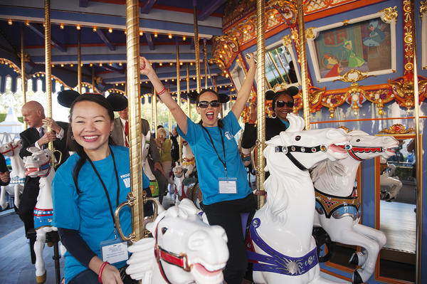Anza Vang, left, Pamela Sailor, center, and Dientre Leon with the Providence Speech and Hearing Center ride the King Arthur Carrousel at Disneyland.
