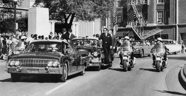 Seen through the foreground convertible's windshield, President John F. Kennedy's hand reaches toward his head within seconds of being fatally shot.