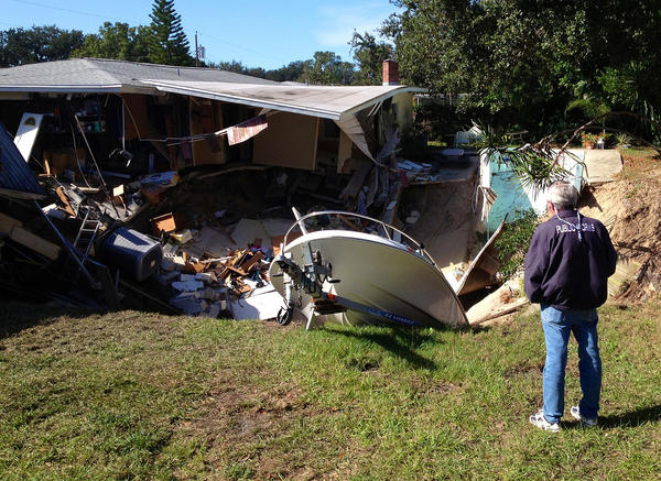 A man observes a sinkhole has swallowed parts of two houses in Dunedin, Fla. on Thursday, Nov. 14, 2013. Dunedin Deputy Fire Chief Trip Barrs said the hole appeared to be about 12-feet wide when officials arrived on the scene. Residents of the neighboring houses also were evacuated as a precaution. There are no reports of injuries. (AP Photo/The Tampa Tribune, Luke Johnson) ST. PETERSBURG OUT; LAKELAND OUT; BRADENTON OUT; MAGS OUT; LOCAL TV OUT; WTSP CH 10 OUT; WFTS CH 28 OUT; WTVT CH 13 OUT; BAYNEWS 9 OUT; THE TAMPA BAY TIMES OUT; LAKELAND LEDGER OUT; BRADENTON HERALD OUT; SARASOTA HERALD-TRIBUNE OUT; WINTER HAVEN NEWS CHIEF OUT ** Usable by LA and DC Only **
