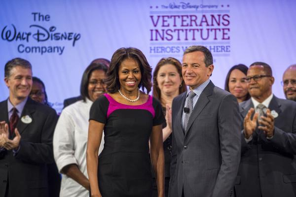 "LAKE BUENA VISTA, FL - NOVEMBER 14: Disney Chairman and CEO Robert A. Iger and First Lady Michelle Obama address the audience at Disney's BoardWalk Resort at Walt Disney World Resort November 14, 2013 in Lake Buena Vista, Florida. Iger and Obama gave keynote remarks at Disney's first-ever ""Veterans Institute"" workshop. The complimentary day-long seminar, co-sponsored by Disney's ""Heroes Work Here"" initiative and the Disney Institute, is designed to help companies build effective veteran-hiring programs of their own. (Photo by Matt Stroshane/Disney Parks via Getty Images) ** OUTS - ELSENT, FPG, TCN - OUTS * NM, PH, VA if sourced by CT, LA or MoD **"