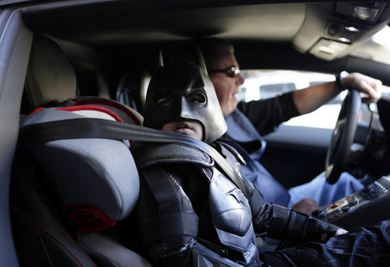 "Miles Scott waits in the Batmobile before thwarting a ""robbery"" in San Francisco. Miles has battled a very tough foe in his personal life: leukemia. After his cancer went into remission, the Make-A-Wish Foundation helped him become Batkid for a day."