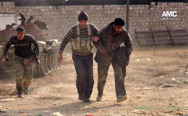 Two Free Syrian Army fighters help a wounded comrade during clashes in Aleppo, Syria.