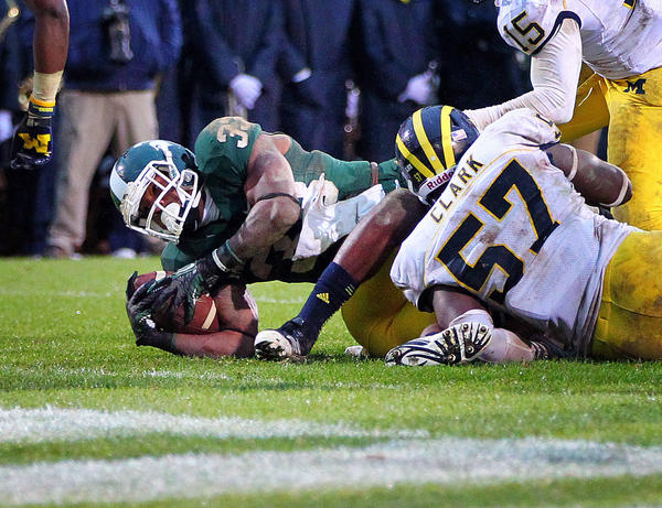 Michigan State's Jeremy Langford stretches for extra yards against Michigan's Frank Clark.