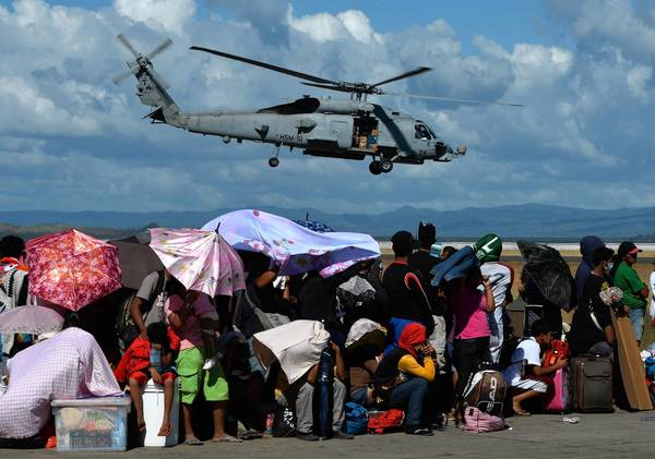 A U.S. Navy helicopter flies over the Tacloban airport. With a U.N. agency now putting the death toll at 4,460, the Philippine government is under fire for what critics say is the slow pace of its official relief effort.