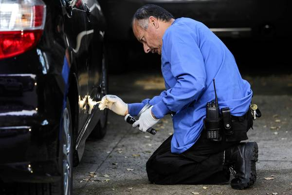 An LAPD print specialist dusts a Honda Fit for prints in the 2300 block of Moreno Drive on Thursday. The vehicle was broken into the evening before state Assemblyman Mike Gatto's father was found dead in a nearby home.