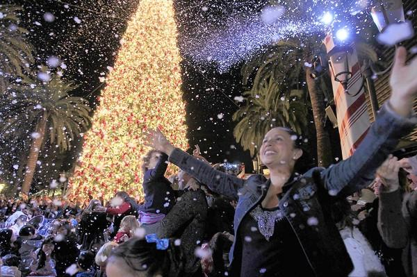 Guests enjoy the snowfall during the annual Fashion Island Christmas tree lighting ceremony in Newport Beach on Friday.