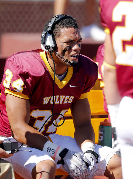 Northern State University's Logan Dosch talks to a coach on the headset from the sideline during a game against Upper Iowa at Swisher Field in September.